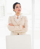 Stern businesswoman standing behind her chair Royalty Free Stock Photos