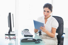 Stern businesswoman using her digital tablet at desk Stock Images