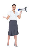 Stern businesswoman yelling in her megaphone Stock Photos