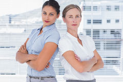 Stern businesswomen standing back to back Royalty Free Stock Photo