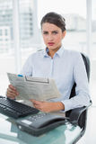 Stern classy brown haired businesswoman reading a newspaper Stock Images