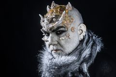 Stern demon with pale white skin tinted with gold. Evil creature controlling snow and frost, winter god. Monster with. Thorns on face wearing fur collar stock image