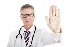 Stern doctor holding up his hand in a Halt gesture Royalty Free Stock Images