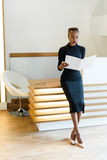 Stern elegant business woman wearing black dress and beige shoes in light office looking at her agenda, full length portrait Royalty Free Stock Image