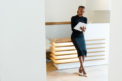 Stern elegant business woman wearing black dress and beige shoes in light office looking at her agenda, full length portrait Royalty Free Stock Photo
