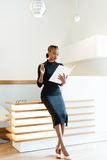 Stern elegant business woman wearing black dress and beige shoes in light office looking at her agenda, full length portrait Royalty Free Stock Photography