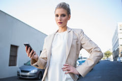 Stern elegant businesswoman holding smartphone Stock Photos