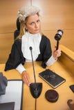 Stern judge banging her hammer Stock Photo