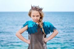 Stern little princess girl in the crown watch frowningly, stands akimbo. Stern but cute little princess girl in the crown watch frowningly, stands akimbo stock images