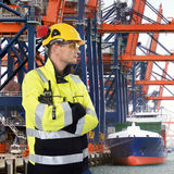Stern looking Docker. Docker, wearing a hard hat, gloves, safety glasses and a chemical resistant coat, sternly overlooking  an industrial harbor with large Stock Photo