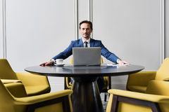Stern male manager working at round desk. Portrait of successful businessman sitting at round table for negotiations. He is looking forward seriously. Laptop and Stock Photo