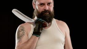 Stern man with beard, tattoo in T-shirt in black studio holding cleaver. Closeup