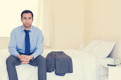 Stern man looking at camera sitting on his bed Royalty Free Stock Photos