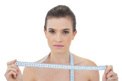 Stern natural brown haired model holding a measuring tape Royalty Free Stock Photos