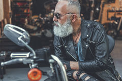 Stern old man ready for using motorbike. Serious bearded elder biker is waiting for someone while sitting on motorcycle. He glancing aside with determination stock image