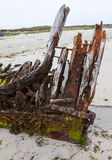 Stern Post of Wrecked wooden sailing ship. Stern post of a wrecked sailing ship covered in seaweed with rusting metal fittings.  Taken on the island of Tiree in Royalty Free Stock Image