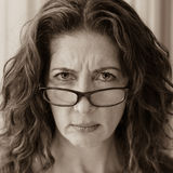 Stern School Teacher. Middle aged female teacher frowning over her glasses stock photo