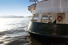 Stern of a seagoing vessel. Probably either a yacht or small ferry, with an open viewing deck with a life preserver and a view past the rear to the coastline Stock Photo