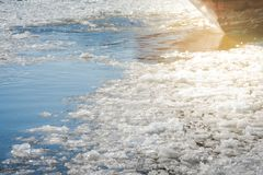 Stern of ship sailing along a river covered with ice floes in ea Stock Image