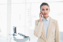 Stern smart brown haired businesswoman calling with her mobile phone Stock Image