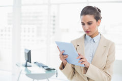 Stern smart brown haired businesswoman looking at a tablet pc Royalty Free Stock Photos