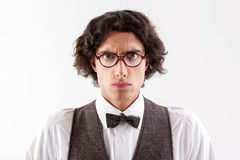 Stern smart guy expressing his seriousness. Waist up portrait of serious young man looking at camera scrupulously. He is wearing eyeglasses. Isolated Stock Images