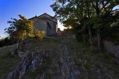 Stern sprengte Sonne durch Bäume mit Provence-Kirche Stockbild
