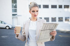 Stern stylish businesswoman reading newspaper Royalty Free Stock Image