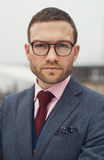Stern stylish young businessman. Wearing glasses staring intently at the camera with a troubled frown, close up head and shoulders Stock Photography