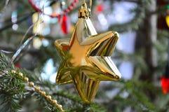 Stern-Weihnachtsspielzeug, das am Baum hängt Stockfoto