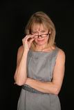 Stern woman looking over glasses. Older woman looking over top of glasses Royalty Free Stock Images