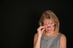 Stern woman looking over glasses. Older woman looking over top of glasses Royalty Free Stock Image