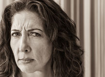 Stern Woman Portrait. Middle aged woman frowning and looking askance at the viewer Royalty Free Stock Image