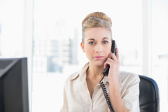 Stern young blonde businesswoman answering the telephone Stock Photography