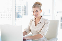 Stern young blonde businesswoman using a laptop Royalty Free Stock Image