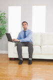 Stern young businessman using his laptop while sitting on cosy s Stock Photo