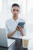 Stern young businesswoman holding a calculator sitting at her desk Royalty Free Stock Images