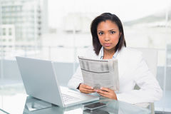 Stern young dark haired businesswoman holding a document Stock Photo
