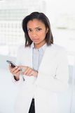 Stern young dark haired businesswoman using a mobile phone Stock Photos