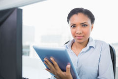 Stern young dark haired businesswoman using a tablet pc Royalty Free Stock Photo