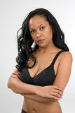 Stern Young Woman. A stern looking, young African-American woman has her arms crossed and is wearing a black sports bra with a look of displeasure Royalty Free Stock Photo