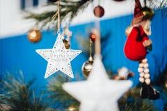 Sterndekoration, die am Weihnachtsbaum hängt lizenzfreie stockbilder