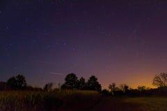 Sterne über den Wald- und Dorflichtern in der rechten Ecke Stockfoto