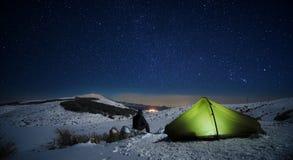 Sternenklare Nacht auf dem Mann, der Winter-Landschaft durch das Beleuchten des Zeltes schaut stockbild