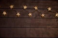 Sternenklare Weihnachtslichter auf einem grauen hölzernen Hintergrund stockfotografie