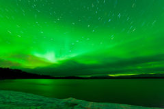 Sternenklarer nächtlicher Himmel des aurora borealis über See Laberge Stockfoto