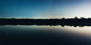 Sternenklarer nächtlicher Himmel reflektiert im See Lizenzfreies Stockfoto