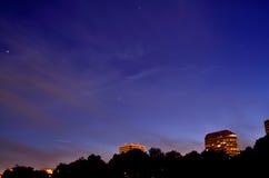 Sternenklarer nächtlicher Himmel über Stadt Stockbild