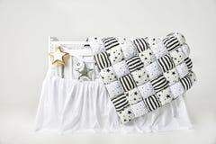 Sternförmige Kissen des Silbers und des Goldes und Patchworkdeckbett auf einem weißen Babyfeldbett Lizenzfreies Stockfoto