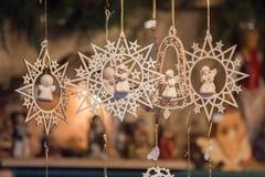 Sternförmige und glockenförmige hölzerne Weihnachtsverzierungen und kleine Engel Lizenzfreie Stockfotografie